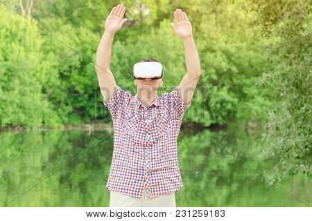 Man In Helmet Of Virtual Reality Against The Background Of Nature. Hands Up