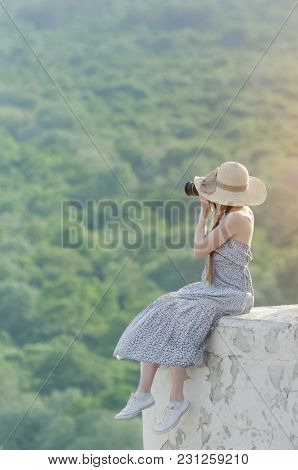 Young Women Sits On A Hill And Takes Pictures Against A Forest