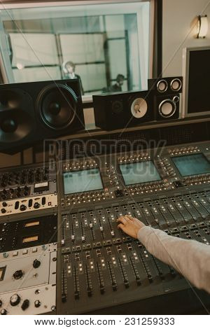Cropped Shot Of Sound Producer Working With Graphic Equalizer At Studio