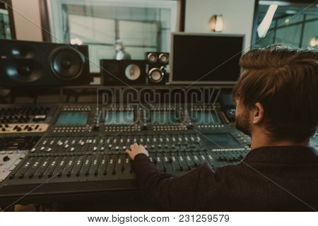 Handsome Young Sound Producer Working At Recording Studio