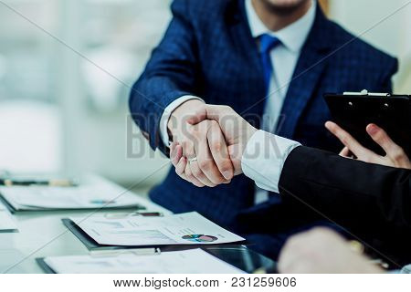 Closeup Of Handshake Of Business Partners After Discussion Of The Financial Agreement On The Backgro