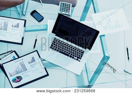 Financial Charts, Marketing Diagrams, Laptop And Calculator At The Workplace Of The Businessman .