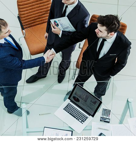 Top View - Handshake Of Business Partners Before Considering A New Financial Agreement Near The Desk