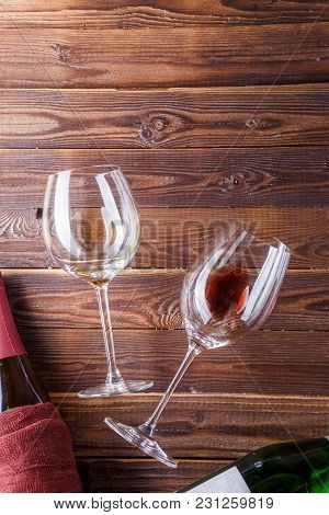 Image Of Two Wine Bottles And Wine Glasses On Brown, Wooden Background. Empty Place For Text.