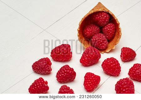 Ripe Sweet Raspberries In Ice Cream Waffle Cone, Copy Space. Fresh Berries On White Wooden Backgroun
