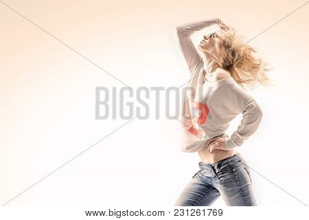 Beautiful Young Blonde Woman In A Vest And Jeans On A White Background With Energetic Dance Moves St