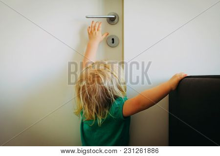 Kids Safety Concept- Little Girl Try To Reach Door Handle