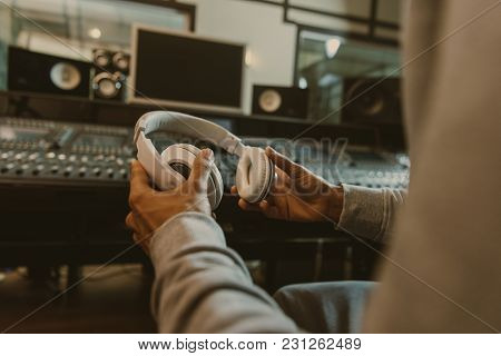 Cropped Shot Of Sound Producer With Headphones Sitting At Studio