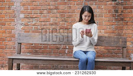 Woman look at mobile phone at school
