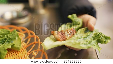 Woman wrapping grilled korean meat in lettuce at restaurant