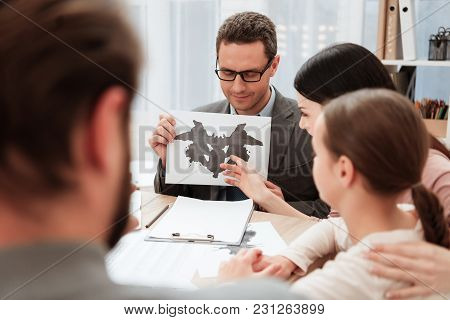 Adult Psychologist Shows Cards With Rorschach Spots To Family Sitting In Office. Family Of Three Vis