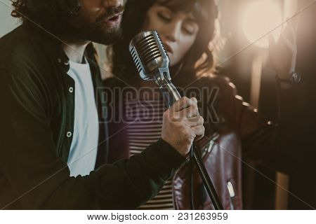 Close-up Shot Of Young Couple Performing Song With Vintage Microphone