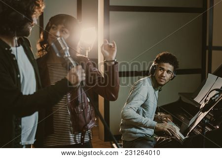 Young Couple Performing Song With Microphone While Man Playing Piano Behind