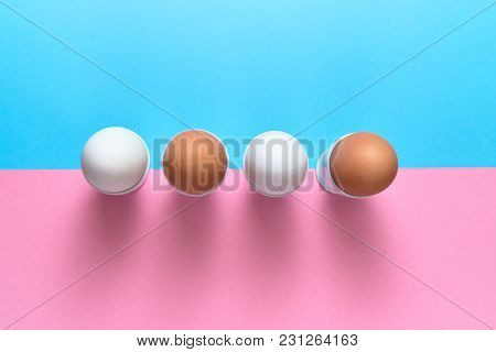 Eggs Standing On Egg Cup On Blue And Pink Pastel Background, Copy Space. Boiled Eggs In Stand On Pap
