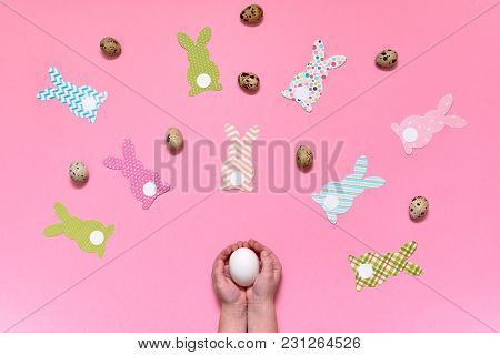 Child Holding In Hands White Egg On Pink Background With Easter Bunny Decorations And Quail Eggs, Co