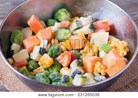 Frozen Vegetables In Bowl On Wooden Table Background. Mixed Vegetables In A Bowl