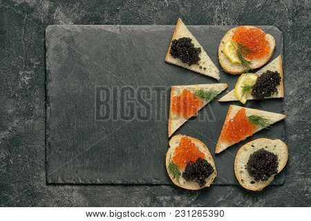 Sandwiges With Red Salmon And Black Stugeon Caviar On A Black Stone Board On A Black Table, Top View