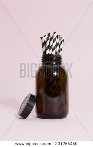 An Old Vintage Pharmacy Glass Bottle Filled With Several Graphic Straws On A Vibrant Pop Pink Backgr