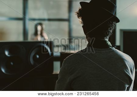 Rear View Of Sound Producer Looking At Singer Recording Song Behind Glass At Studio