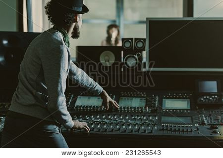 Back View Of Sound Producer In Hat Recording Song At Studio