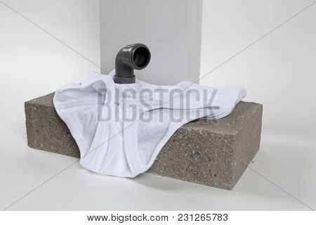 A Metaphor Of Periscope Made With Pipes Emerging From A Y-front Male Underwear On Cinder Block. Mini