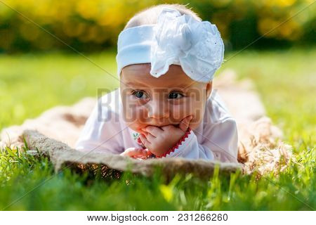A Cute White Infant Lies On The Grass And Sticks His Fingers In His Mouth. Close-up View.