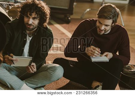Young Music Band Colleagues Writing Lyrics Together While Sitting On Floor