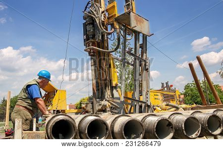 Geothermal Drilling Rig Workers.  Drilling Geothermal Well For A Residential Geothermal Heat Pump.