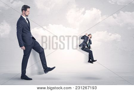 Big businessmen kicking himself as a small employee with cloudy background