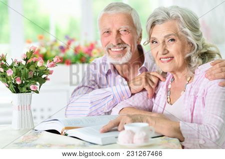 Portrait Of A Happy Senior Couple Reading Book At Home