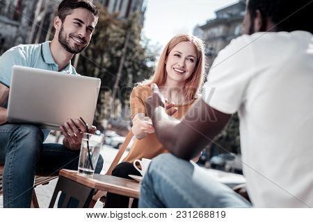 Positive Attitude To Work. Motivated Millennial Entrepreneurs Smiling While Sitting In A Cafe And Wo