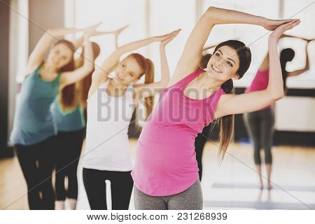 Beautiful Pregnant Women In Yoga Class Standing In A Fitness Studio, Doing Exercise.