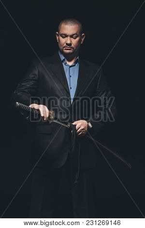 Yakuza Member In Suit Taking Out Katana Sword Isolated On Black
