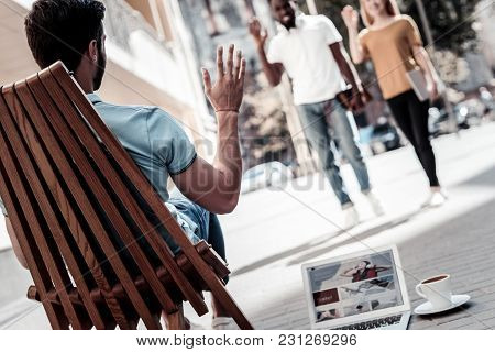Nice To Meet You. Selective Focus On A Turned Back Bearded Guy Welcoming His Mates While Sitting In