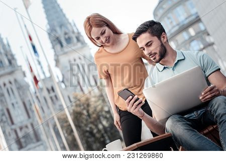 Have You Seen. Low Angle Shot Of Millennial Colleagues Smiling While Looking At A Screen Of A Smartp