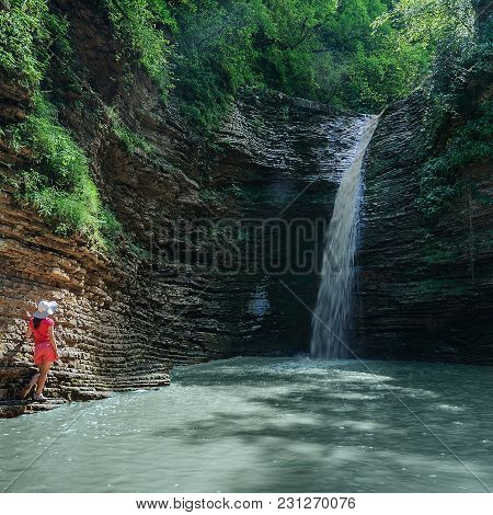 Girl In Red Looks At The Waterfall Maiden Spit On The Stream Rufabgo, Adygea, Russia
