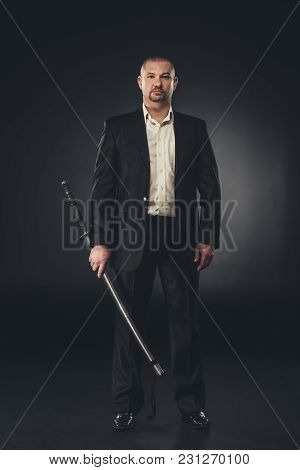 Mature Handsome Man In Suit With Katana On Black