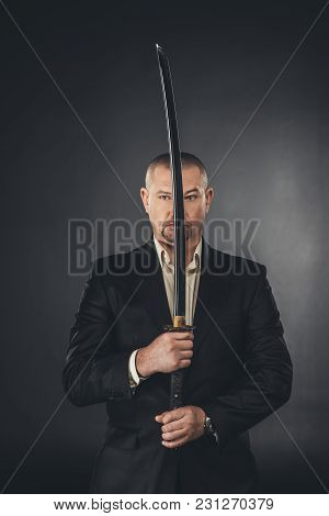 Man In Suit Holding Katana Sword In Front Of His Face On Black