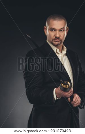 Handsome Mature Man In Suit With Katana Sword On Black