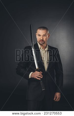 Man In Suit With Katana Sword Looking At Camera On Black