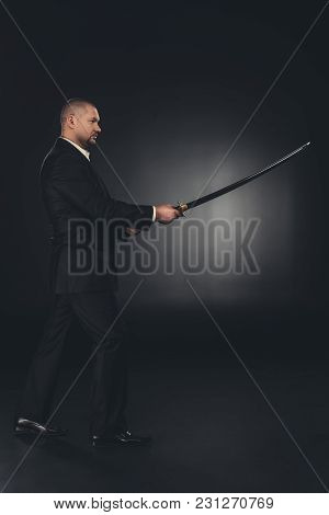 Side View Of Mature Man In Suit With Katana Sword On Dark Background