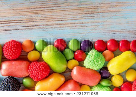 Bright Colored Cho Olate And Gummy Candy On A Blue Wooden Background With Copyspace