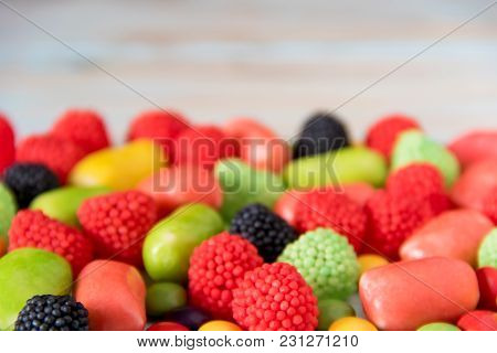 Different Bright Colored Candy On A Blue Wooden Background With Copyspace