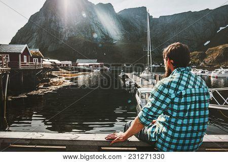 Traveler Man Sitting On Bridge Sightseeing Reine Village In Norway Lifestyle Adventure Outdoor Summe