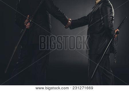 Cropped Shot Of Yakuza Members Shaking Hands With Katanas Behind Back Isolated On Black