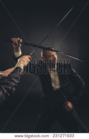 Strong Mature Businessman Fighting With Katana Sword Isolated On Black