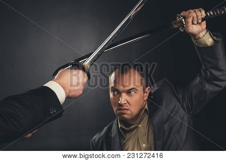 Cropped Shot Of Modern Samurai Fighting With Swords On Black