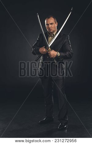 Handsome Man In Suit With Dual Katana Swords On Black