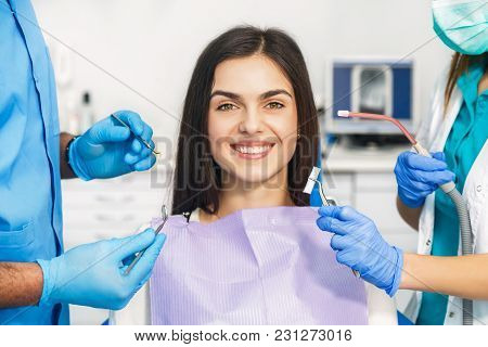 Smiling Beautiful Patient Sitting In Chair With Dental Purple Bib, Male Dentist, In Blue Uniform And