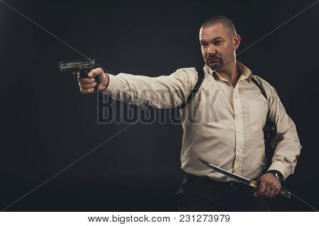Yakuza Member Aiming With Gun While Holding Tanto Knife Isolated On Black
